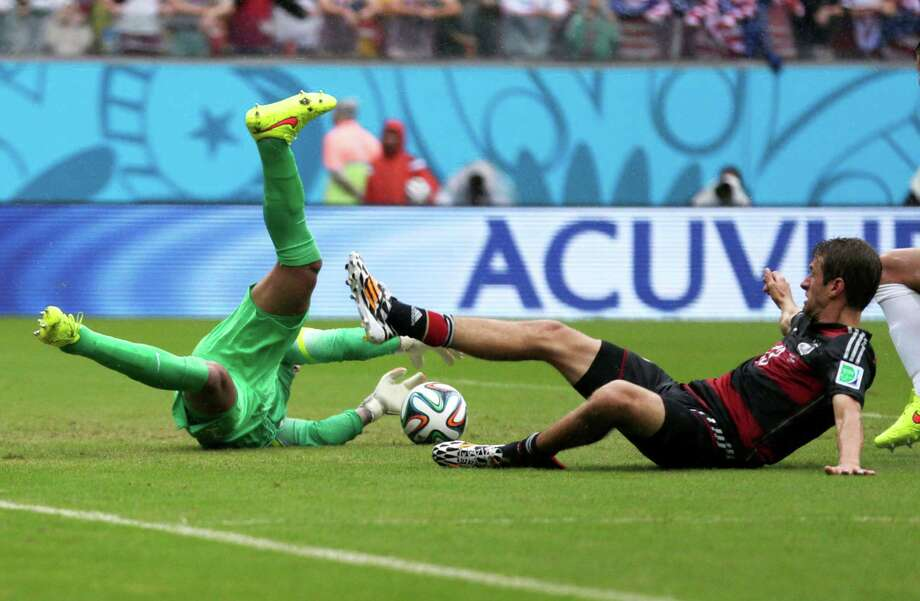 United States' goalkeeper Tim Howard goes down to make a save on Germany's Thomas Mueller during the group G World Cup soccer match between the United States and Germany at the Arena Pernambuco in Recife, Brazil, Thursday, June 26, 2014. (AP Photo/Julio Cortez) Photo: Julio Cortez, Associated Press / AP