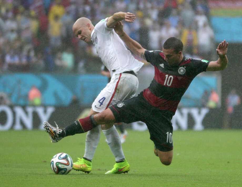 Germany's Lukas Podolski leaps into United States' Michael Bradley to clear the ball during the group G World Cup soccer match between the United States and Germany at the Arena Pernambuco in Recife, Brazil, Thursday, June 26, 2014. (AP Photo/Julio Cortez) Photo: Julio Cortez, Associated Press / AP
