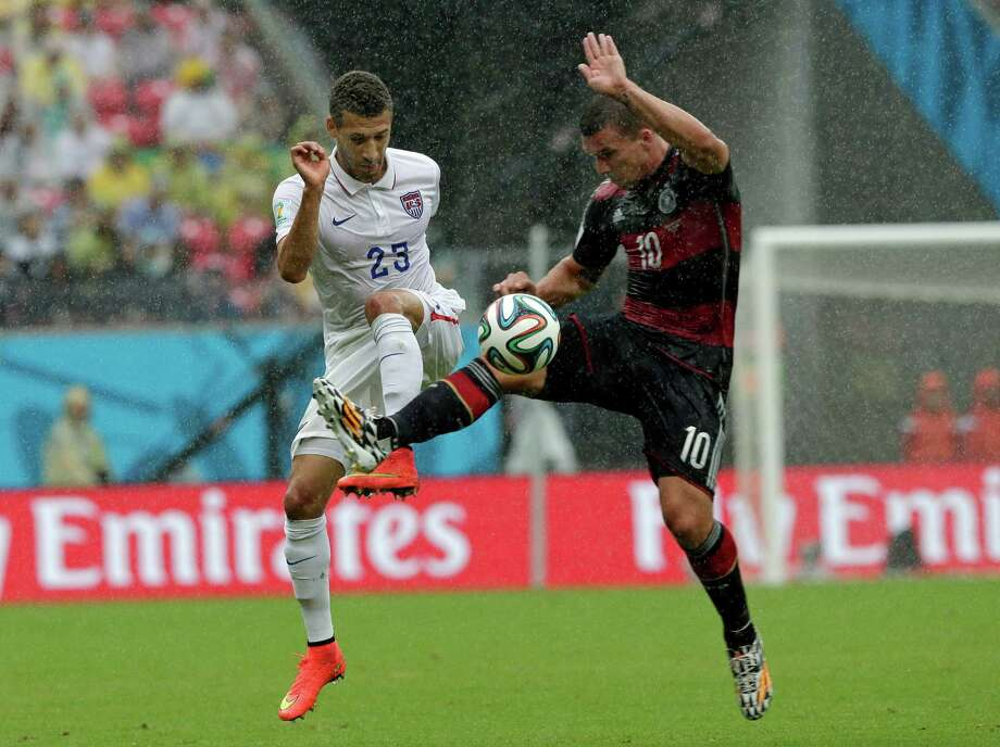 United States' Fabian Johnson, left, and Germany's Lukas Podolski challenge for the ball during the group G World Cup soccer match between the USA and Germany at the Arena Pernambuco in Recife, Brazil, Thursday, June 26, 2014. (AP Photo/Matthias Schrader) Photo: Matthias Schrader, Associated Press / AP