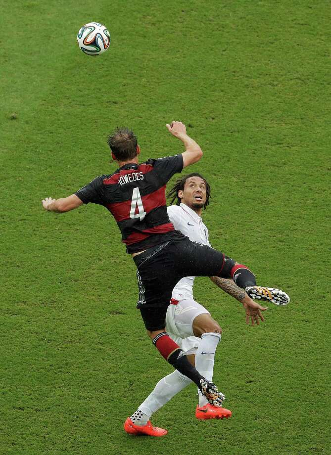 United States' Jermaine Jones watches the ball as Germany's Benedikt Hoewedes goes up for a header during the group G World Cup soccer match between the USA and Germany at the Arena Pernambuco in Recife, Brazil, Thursday, June 26, 2014. (AP Photo/Hassan Ammar) Photo: Hassan Ammar, Associated Press / AP
