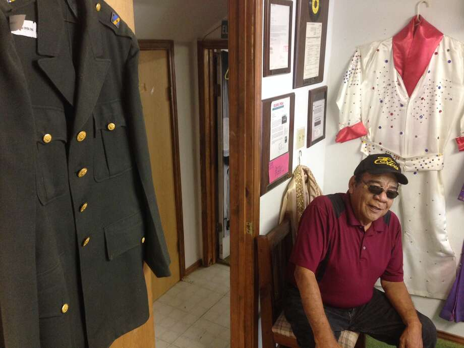 Simon Vega talks about his collection of Elvis Presley memorabilia at Little Graceland in Los Fresnos, June 22, 2015. Pictured with Vega is a military jacket that once belonged to Presley. Photo: J.R. Gonzales