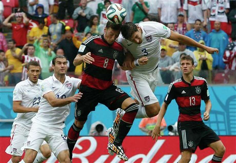 Germany's Mesut Ozil, center,  goes for a header with United States' Omar Gonzalez as United States'  Graham Zusi, left, looks on during the group G World Cup soccer match between the USA and Germany at the Arena Pernambuco in  Recife, Brazil, Thursday, June 26, 2014. (AP Photo/Matthias Schrader)
