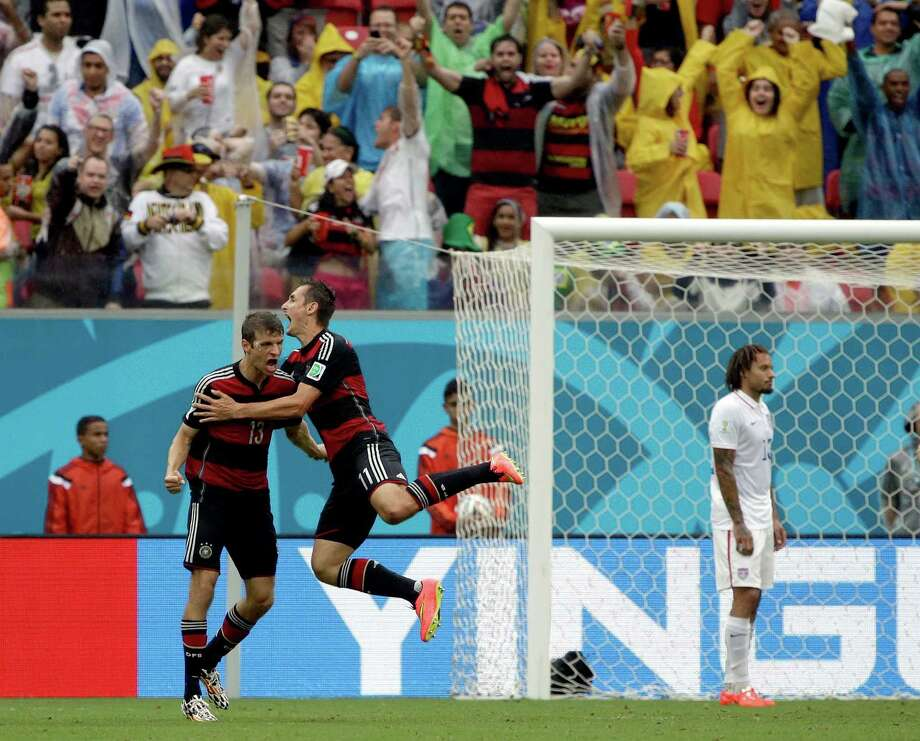 Germany's Thomas Mueller celebrates with his teammate Miroslav Klose, right, after scoring his side's first goal during the group G World Cup soccer match between the United States and Germany at the Arena Pernambuco in Recife, Brazil, Thursday, June 26, 2014. (AP Photo/Ricardo Mazalan) Photo: Ricardo Mazalan, Associated Press / AP2014