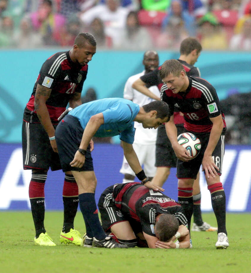 Referee Ravshan Irmatov from Uzbekistan checks on Germany's Bastian Schweinsteiger after an incident with United States' Kyle Beckerman during the group G World Cup soccer match between the United States and Germany at the Arena Pernambuco in Recife, Brazil, Thursday, June 26, 2014. (AP Photo/Julio Cortez) Photo: Julio Cortez, Associated Press / AP