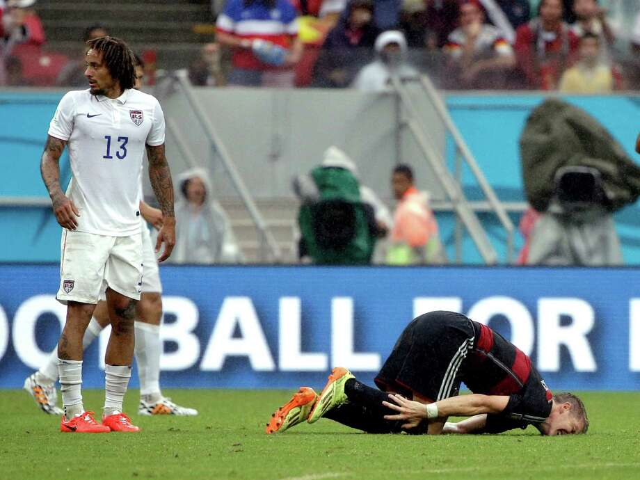 Germany's Bastian Schweinsteiger lies on the ground after an incident with United States' Kyle Beckerman during the group G World Cup soccer match between the USA and Germany at the Arena Pernambuco in Recife, Brazil, Thursday, June 26, 2014. Left is United States' Jermaine Jones. (AP Photo/Ricardo Mazalan) Photo: Ricardo Mazalan, Associated Press / AP