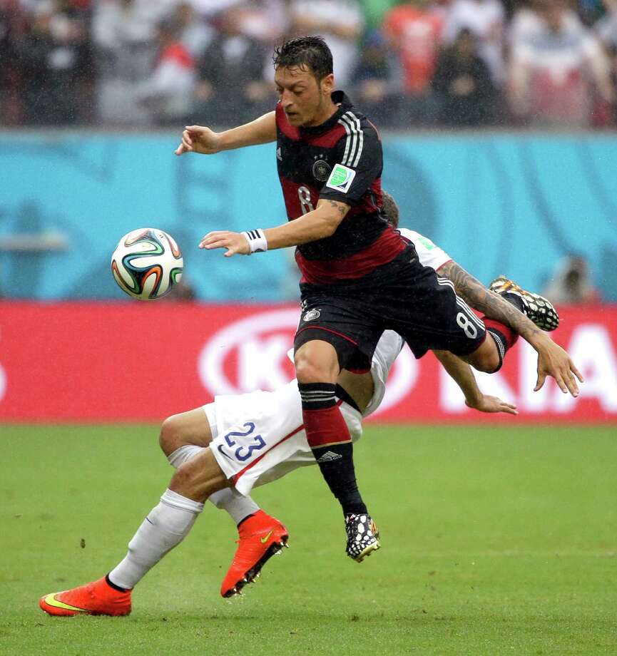 Germany's Mesut Ozil leaps past United States' Fabian Johnson as he attacks during the group G World Cup soccer match between the USA and Germany at the Arena Pernambuco in Recife, Brazil, Thursday, June 26, 2014. (AP Photo/Ricardo Mazalan) Photo: Ricardo Mazalan, Associated Press / AP
