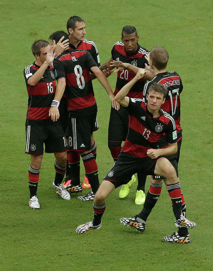 Germany's Thomas Mueller (13) celibates with teammates after he scored during the group G World Cup soccer match between the USA and Germany at the Arena Pernambuco in Recife, Brazil, Thursday, June 26, 2014. (AP Photo/Hassan Ammar) Photo: Hassan Ammar, Associated Press / AP