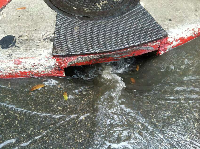 Water rushes into a storm drain at Alamo and 4th streets after storms blew through the San Antonio area late Thursday morning, June 26, 2014.