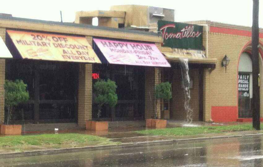 Water cascades from the sign on Tomatillo's restaurant on Broadway as rain falls in the San Antonio area on Thursday, June 26, 2014.