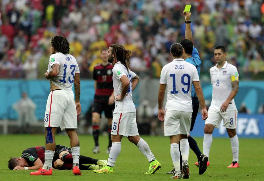 United States' Kyle Beckerman, center, is booked by referee Ravshan Irmatov from Uzbekistan after fouling Germany's Bastian Schweinsteiger, bottom left, during the group G World Cup soccer match between the USA and Germany at the Arena Pernambuco in Recife, Brazil, Thursday, June 26, 2014. (AP Photo/Petr David Josek) Photo: Petr David Josek, Associated Press / AP