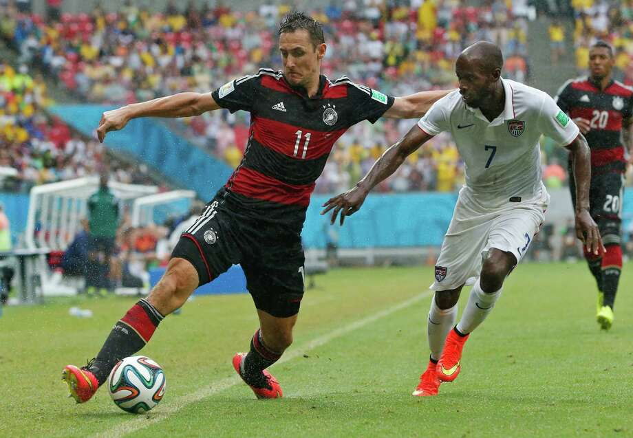 Germany's Miroslav Klose, left, and United States' DaMarcus Beasley challenge for the ball during the group G World Cup soccer match between the USA and Germany at the Arena Pernambuco in Recife, Brazil, Thursday, June 26, 2014. (AP Photo/Matthias Schrader) Photo: Matthias Schrader, Associated Press / AP