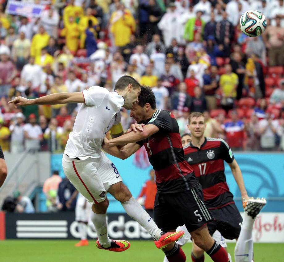 Germany's Mats Hummels pushes off United States' Clint Dempsey as he heads the ball at the Germany goal during the group G World Cup soccer match between the USA and Germany at the Arena Pernambuco in Recife, Brazil, Thursday, June 26, 2014. (AP Photo/Ricardo Mazalan) Photo: Ricardo Mazalan, Associated Press / AP