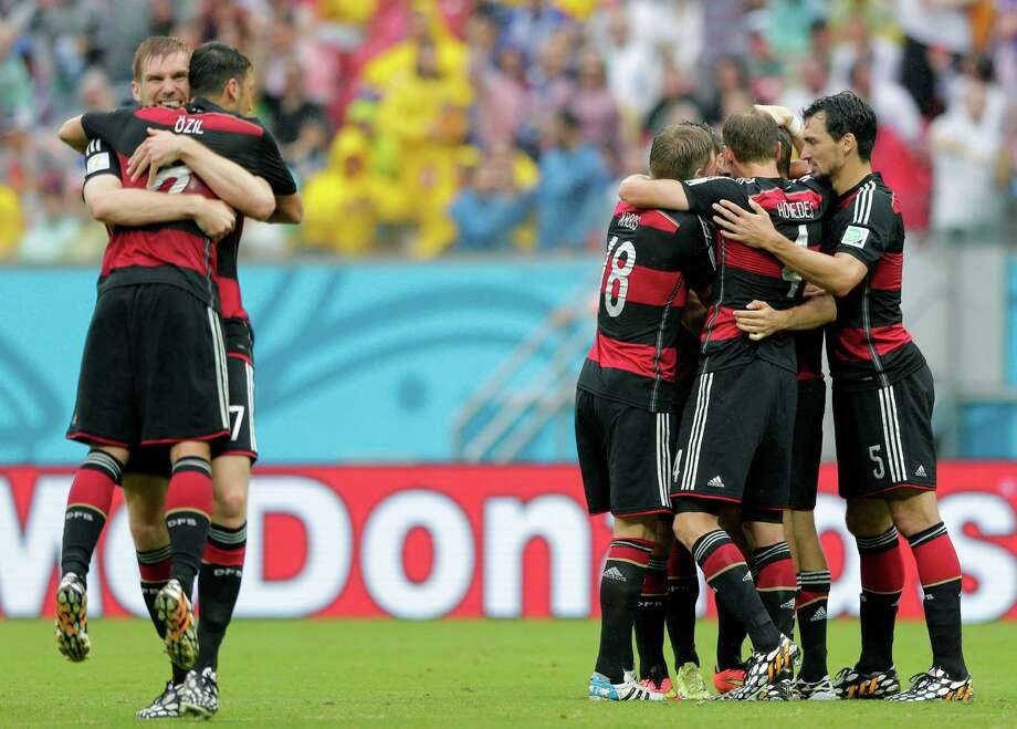 Germany's Per Mertesacker, left, hugs his teammate Mesut Ozil after Germany's Thomas Mueller scored the opening goal during the group G World Cup soccer match between the USA and Germany at the Arena Pernambuco in Recife, Brazil, Thursday, June 26, 2014. (AP Photo/Matthias Schrader) Photo: Matthias Schrader, Associated Press / AP
