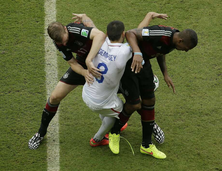 United States' Clint Dempsey (8) gets tangled with Germany's Per Mertesacker, left, and Germany's Jerome Boateng during the group G World Cup soccer match at the Arena Pernambuco in Recife, Brazil, Thursday, June 26, 2014. (AP Photo/Hassan Ammar) Photo: Hassan Ammar, Associated Press