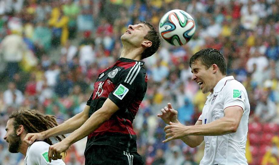 Germany's Thomas Mueller and United States' Matt Besler, right, go for a header during the group G World Cup soccer match between the USA and Germany at the Arena Pernambuco in Recife, Brazil, Thursday, June 26, 2014. (AP Photo/Matthias Schrader) Photo: Matthias Schrader, Associated Press / AP