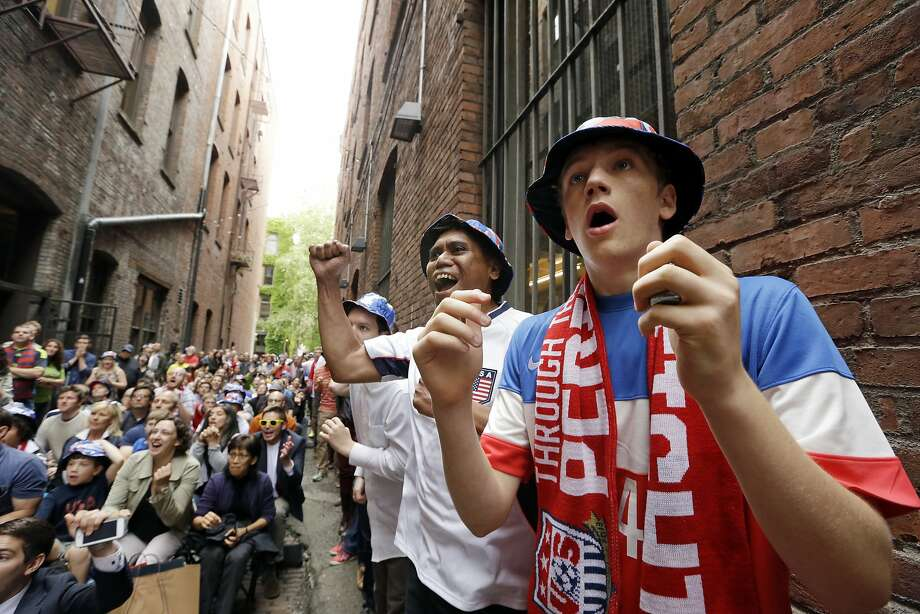 "Ethan Iano, right, and Wil Cabatic react with other fans to an opportunity by the United States as they watch a World Cup soccer match by the team against Germany Thursday, June 26, 2014, from an alley in Seattle's historic Pioneer Square neighborhood. ""Nord Alley"" has been the site of large-screen viewing parties for World Cup games every match day. (AP Photo/Elaine Thompson) Photo: Elaine Thompson, Associated Press"