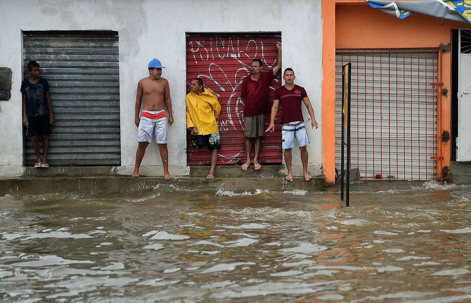People wait to cross a flooded street during a torrential rain in Recife on June 26, 2014 during the 2014 FIFA World Cup in Brazil. AFP PHOTO / PATRIK STOLLARZPATRIK STOLLARZ/AFP/Getty Images Photo: Patrik Stollarz, AFP/Getty Images