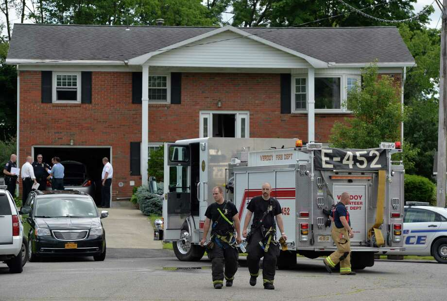 As members of the Verdoy Fire Company return to their fire house, Colonie Police officers and detectives investigate the possible carbon monoxide deaths of two people at 3 Dove Court Thursday afternoon, June 26, 2014, in Colonie, N.Y.  (Skip Dickstein / Times Union) Photo: SKIP DICKSTEIN