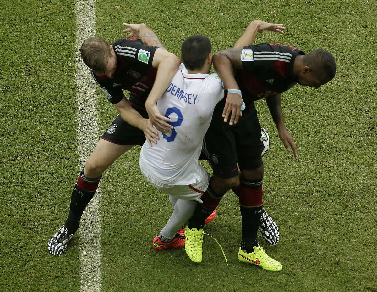 United States' Clint Dempsey (8) gets tangled with Germany's Per Mertesacker, left, and Germany's Jerome Boateng during the group G World Cup soccer match at the Arena Pernambuco in Recife, Brazil, Thursday, June 26, 2014.