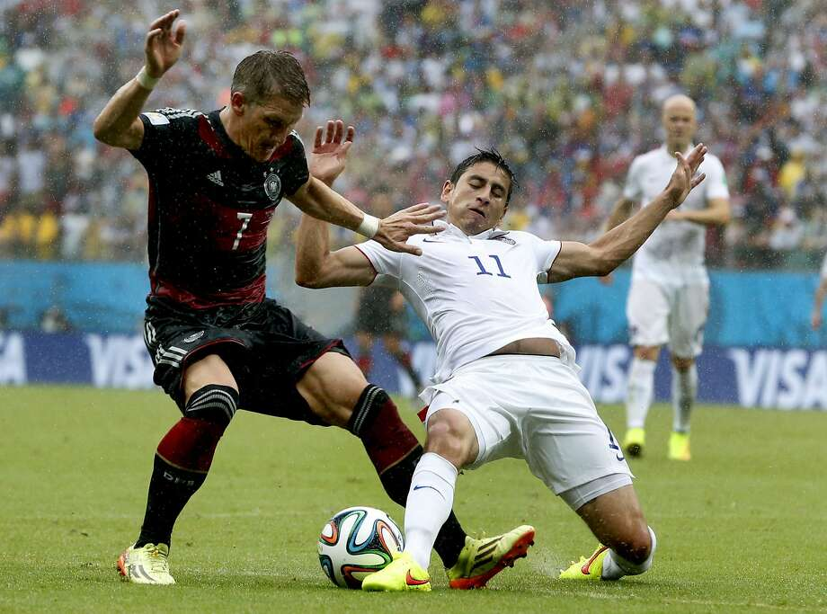 Germany's Bastian Schweinsteiger, left, is challenged by United States' Alejandro Bedoya, right, during the group G World Cup soccer match between the USA and Germany at the Arena Pernambuco in Recife, Brazil, Thursday, June 26, 2014. Photo: Matthias Schrader, Associated Press