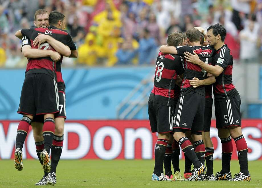 Germany's Per Mertesacker, left, hugs his teammate Mesut Ozil after Germany's Thomas Mueller scored the opening goal during the group G World Cup soccer match between the USA and Germany at the Arena Pernambuco in Recife, Brazil, Thursday, June 26, 2014. Photo: Matthias Schrader, Associated Press