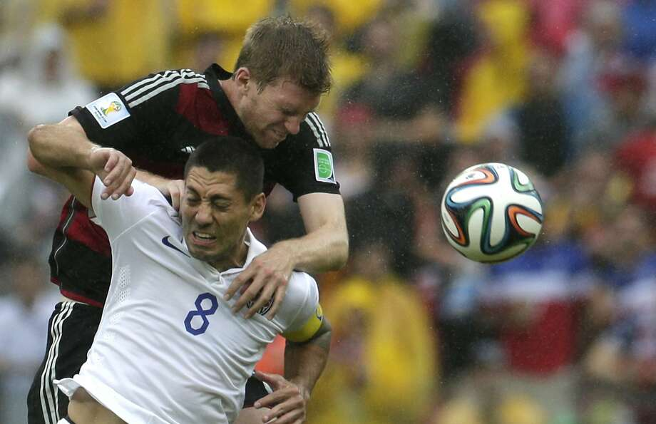 Germany's Per Mertesacker, back, and United States' Clint Dempsey go for a header during the group G World Cup soccer match between the USA and Germany at the Arena Pernambuco in Recife, Brazil, Thursday, June 26, 2014. Photo: Petr David Josek, Associated Press