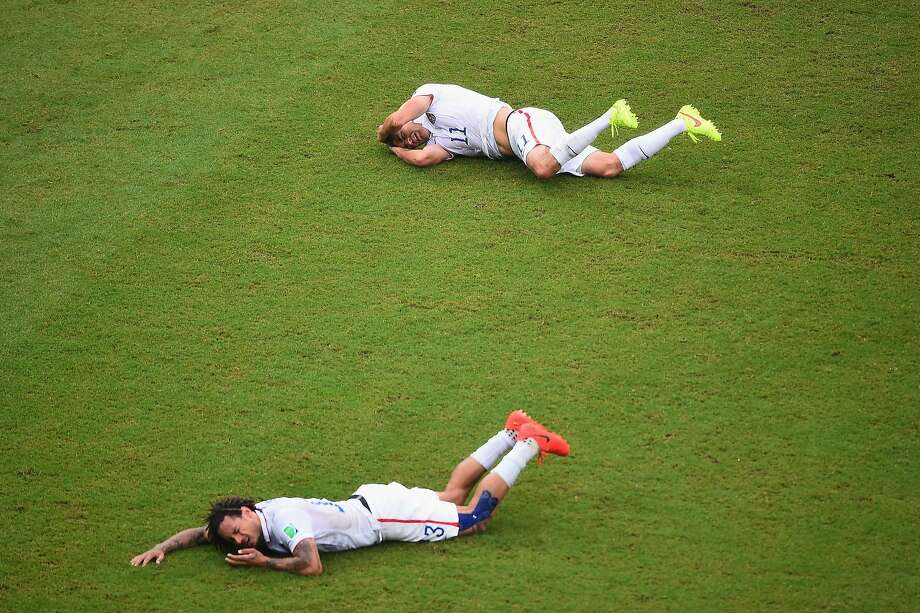 Jermaine Jones (front) of the United States and teammate Alejandro Bedoya lie on the field after colliding during the 2014 FIFA World Cup Brazil group G match between the United States and Germany at Arena Pernambuco on June 26, 2014 in Recife, Brazil. Photo: Laurence Griffiths, Getty Images
