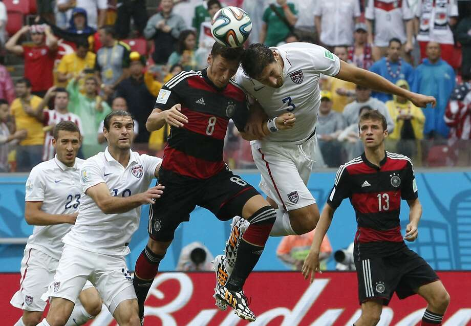 Germany's Mesut Ozil, center, goes for a header with United States' Omar Gonzalez as United States' Graham Zusi, left, looks on during the group G World Cup soccer match between the USA and Germany at the Arena Pernambuco in Recife, Brazil, Thursday, June 26, 2014. (AP Photo/Matthias Schrader) Photo: Matthias Schrader, Associated Press