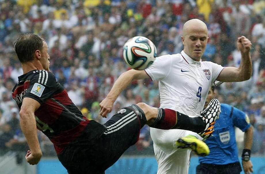 Germany's Benedikt Hoewedes, left, and United States' Michael Bradley challenge for the ball during the group G World Cup soccer match between the USA and Germany at the Arena Pernambuco in Recife, Brazil, Thursday, June 26, 2014. Photo: Matthias Schrader, Associated Press