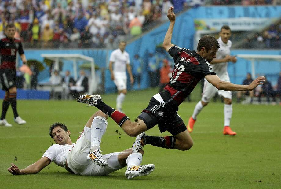 Germany's Thomas Mueller is tripped by United States' Omar Gonzalez during the group G World Cup soccer match between the USA and Germany at the Arena Pernambuco in Recife, Brazil, Thursday, June 26, 2014.  Photo: Ricardo Mazalan, Associated Press