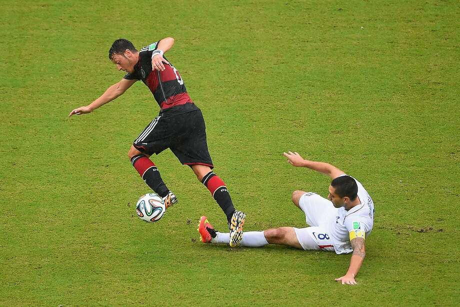 Clint Dempsey of the United States tackles Mesut Oezil of Germany during the 2014 FIFA World Cup Brazil group G match between the United States and Germany at Arena Pernambuco on June 26, 2014 in Recife, Brazil.  Photo: Laurence Griffiths, Getty Images