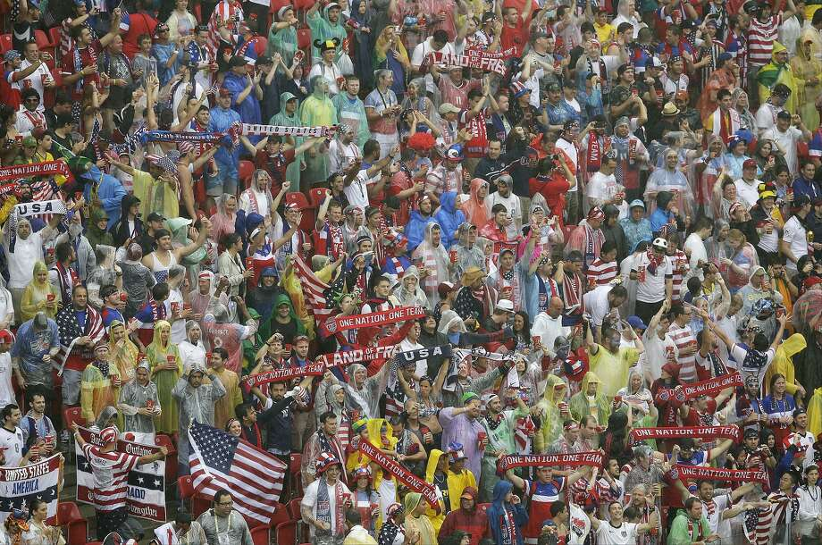 American fans cheer in the rain before the group G World Cup soccer match between the USA and Germany at the Arena Pernambuco in Recife, Brazil, Thursday, June 26, 2014.  Photo: Hassan Ammar, Associated Press