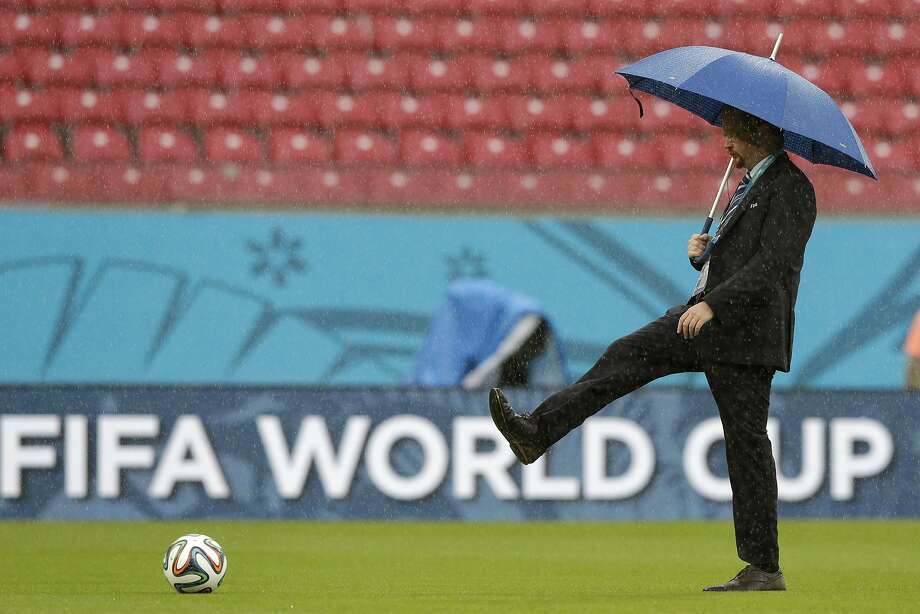 A FIFA official tests the pitch as rain pours down prior to the group G World Cup soccer match between the USA and Germany at the Arena Pernambuco in Recife, Brazil, Thursday, June 26, 2014. (AP Photo/Matthias Schrader) Photo: Matthias Schrader, Associated Press