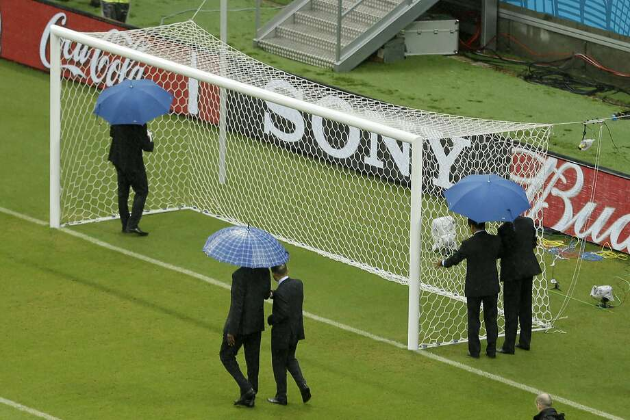 The referees check out the goal prior to the group G World Cup soccer match between the USA and Germany at the Arena Pernambuco in Recife, Brazil, Thursday, June 26, 2014. (AP Photo/Hassan Ammar) Photo: Hassan Ammar, Associated Press
