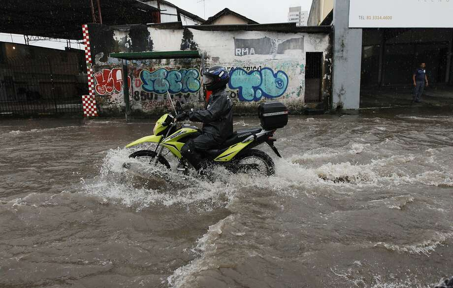 A motorcyclist makes his way down a flooded street after heavy rain storms in Recife, Brazil, Thursday, June 26, 2014. The World Cup soccer match between the USA and Germany will be played at the Arena Pernambuco in Recife today.  (AP Photo/Petr David Josek) Photo: Petr David Josek, Associated Press