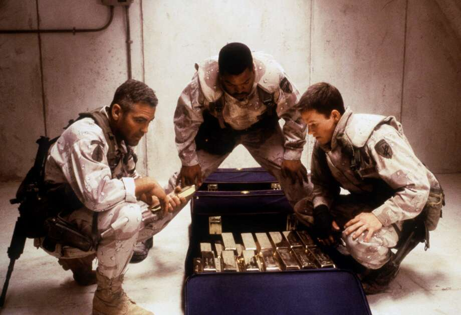 From left, actors George Clooney, Ice Cube and Mark Wahlberg scheme to steal Saddam Hussein's plundered gold in Warner Bros.' Gulf War action film, 'Three Kings.' (AP Photo/Warner Bros., Murray Close) Photo: MURRAY CLOSE / WARNER BROS.