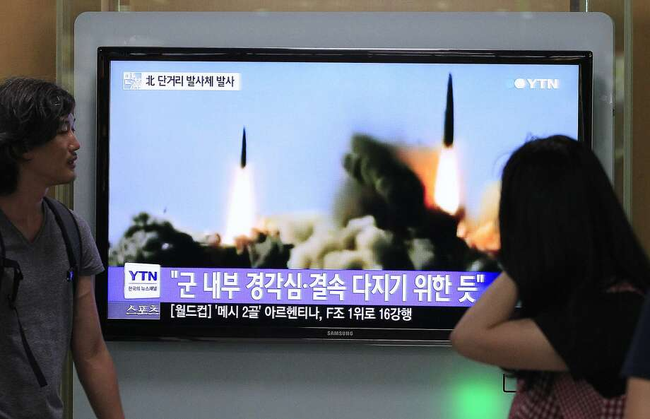 "People watch a TV news program showing the missile launch conducted by North Korea, at Seoul Railway Station in Seoul, South Korea, Thursday, June 26, 2014. North Korea fired three short-range projectiles Thursday into the waters off its east coast, a South Korean defense official said. The move was most likely a routine test-firing, but the official said it could also be meant to stoke tensions with Seoul. The writing on the screen reads ""The missiles were launched to alert and express its internal solidarity."" (AP Photo/Ahn Young-joon) Photo: Ahn Young-joon, Associated Press"