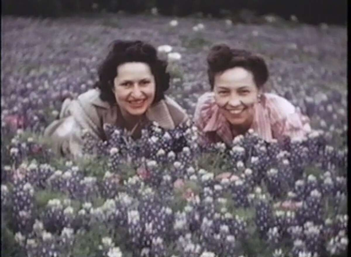 Lady Bird Johnson and her friend Gene Lasseter pose in a field of bluebonnets near Austin in 1943, from the Lady Bird Johnson Home Movies. Johnson was instrumental in both Texas and the nation enacting beautification acts that limited signs on highways.