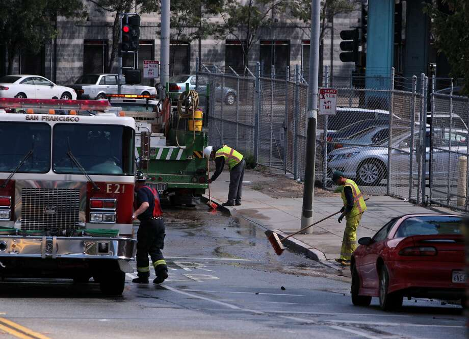 San Francisco Fire and Water department workers remove standing water and debris near the site of a water main break at Bryant and Alameda streets. Photo: Kevin N. Hume, The Chronicle