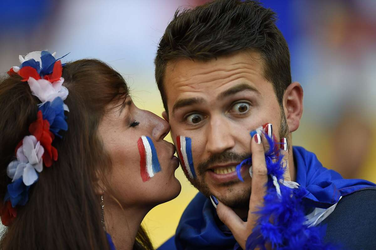 French kissing: A French fan seems surprised by a buss on the cheek before the start of the World Cup match between Ecuador and France in Rio de Janeiro.