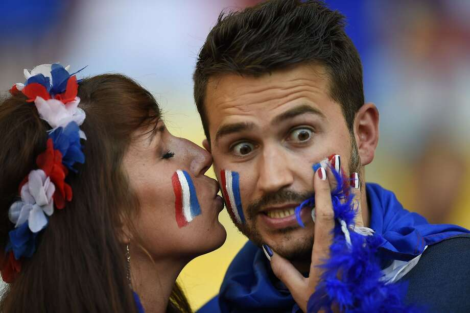 French kissing:A French fan seems surprised by a buss on the cheek before the start of the World Cup match between Ecuador and France in Rio de Janeiro. Photo: Odd Andersen, AFP/Getty Images