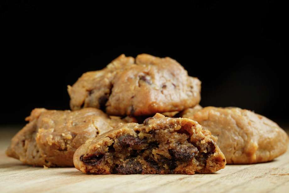 Stories of how the chocolate chip cookie was invented vary, but here's one:In  1930, Ruth Wakefield was baking at her Massachusetts Inn, named the  Toll House Inn. She realized too late that she was not in possession of  any baking chocolate, so she mashed up a chocolate bar and threw the  chunks into the dough. The chocolate stayed solid resulting in a new  cookie. - shebudgets.com Photo: Michael Paulsen, Staff / © 2013 Houston Chronicle