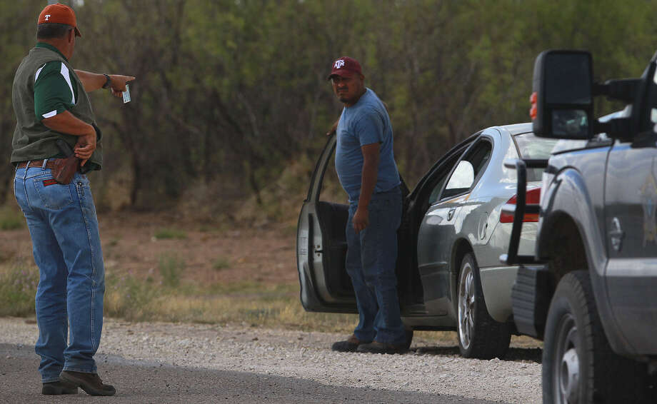 Jeff Davis County Sheriff Rick McIvor (left) pulls over a motorist on U.S. 90 in Valentine. Tongue in cheek, a reader points out something he hopes does not indicate bias on the part of the sheriff. Photo: John Davenport / San Antonio Express-News / ©San Antonio Express-News/John Davenport