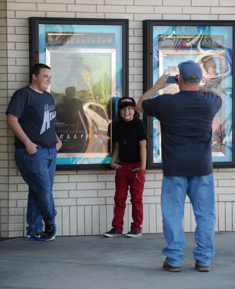 "Dalton Sutton, left, and Deke Garner, center, young actors with parts in ""Hellion,"" get their photo made with the movie's poster by Keith Garner outside Central Mall 10 cinemas on Tuesday afternoon. The Central Mall 10 cinema in Port Arthur hosted two showings of the movie ""Hellion"" on Tuesday evening. Writer and director Kat Candler, producer Kelly Williams, and other crew and cast members attended the premiere of the locally shot film. Photo taken Tuesday 6/10/14 Jake Daniels/@JakeD_in_SETX"
