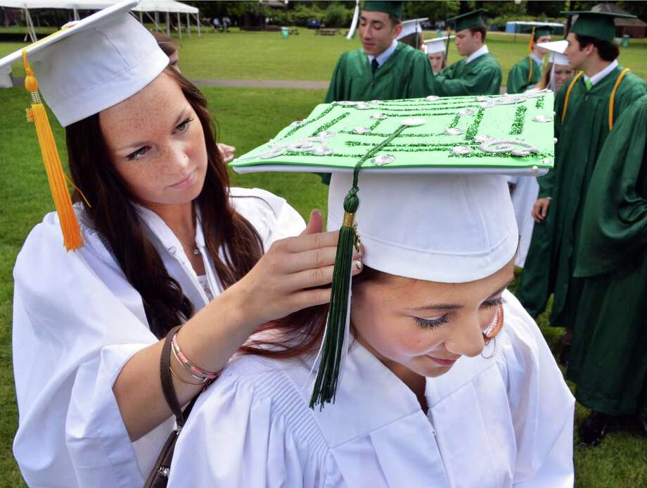 Shenendehowa student Maren Saddler, left, helps classmate Sara Santorelli as they ready for commencement ceremonies at Saratoga Performing Arts Center Thursday June 26, 2014, in Saratoga Springs, NY.  (John Carl D'Annibale / Times Union) Photo: John Carl D'Annibale / 00027259A