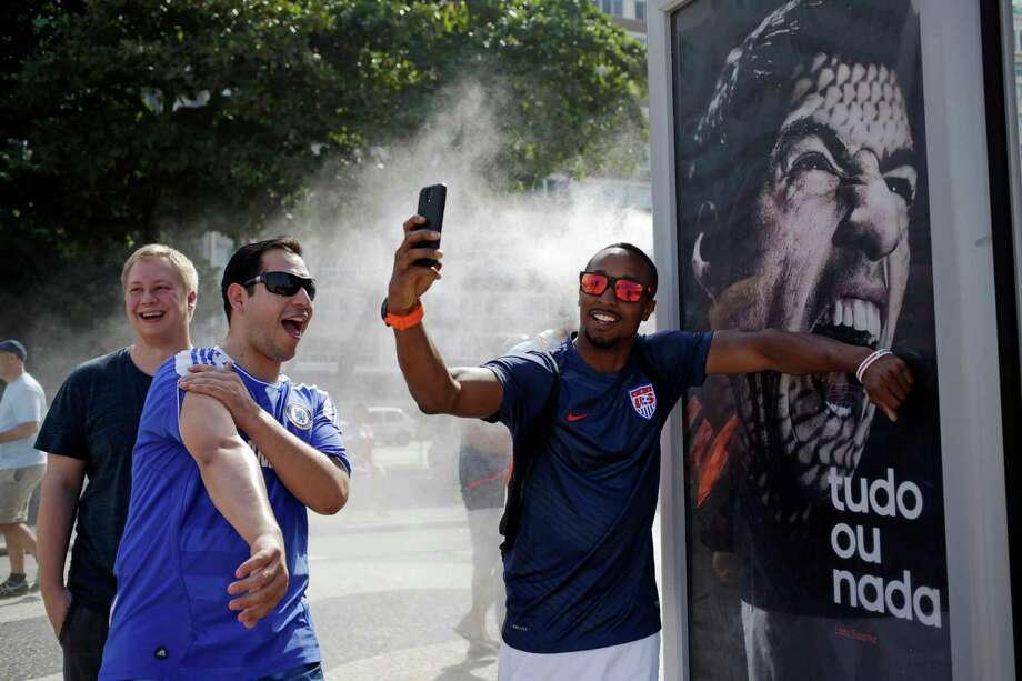 A U.S. soccer fan pretends that Uruguay's soccer striker Luis Suarez is biting him as he takes a selfie next to an Adidas advertisement featuring Suarez near Copacabana beach in Rio de Janeiro, Brazil, Thursday, June 26, 2014. FIFA banned Suarez from all football activities for four months on Thursday for biting an opponent at the World Cup, a punishment that rules him out of the rest of the tournament. (AP Photo/Matt Dunham) Photo: Matt Dunham, Associated Press / AP
