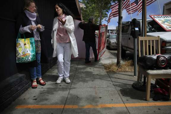 Christian (left) and Ericka Hathaway of Belmont talk behind a line for a 25 foot buffer zone outside of  Planned Parenthood on Valencia Street as Ross Foti of Belmont arranges photos and signs as he demonstrates on Thursday, June 26, 2014  in San Francisco, Calif.