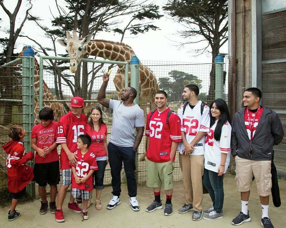 "San Francisco 49ers linebacker Patrick Willis and the winners of the Day at the Zoo contest feed a giraffe at San Francisco Zoo on Wednesday, June 25, 2014. Photo: Marianne Hale, San Francisco Zoo / ""Pacifica Arts, Inc."""