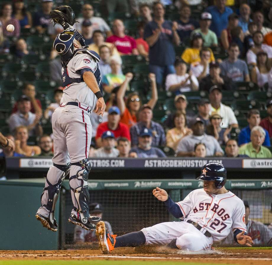 Astros second baseman Jose Altuve (27) scores on a double by Jon Singleton as the throw gets away from Atlanta Braves catcher Gerald Laird (11) during the first inning. Photo: Smiley N. Pool, Houston Chronicle