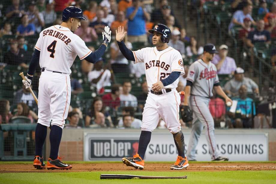 Braves starting pitcher Mike Minor walks away in the background as Astros second baseman Jose Altuve (27) celebrates with George Springer after scoring on a double by Jon Singleton during the first inning. Photo: Smiley N. Pool, Houston Chronicle